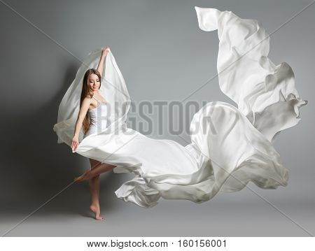 Beautiful Young Girl Dancing. The Girl In Flying White Dress. A White Cloth Is Flying In The Air. Wh