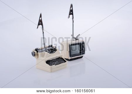Retro Syled Tiny Television And Typewriter Model On White Background