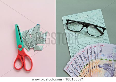 Business, savings and debt money concept : Credit card pieces with scissors on pink background and savings account passbook, glasses, Thai money baht on gray background