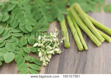 Moringa leaf, flowers and drumstick on a wooden background