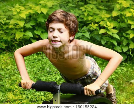Young boy doing push-ups on a portable trainer outdoors in the countryside as he does his training exercises frontal view