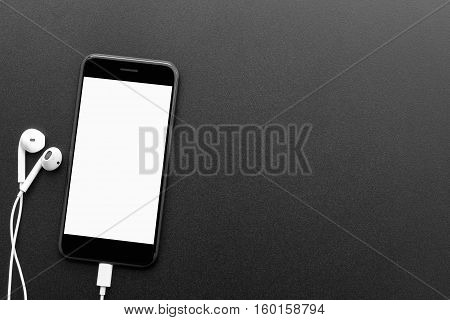 black phone and headphones on table top view with copyspace