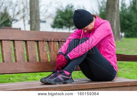 Young athlete woman tired or depressed resting on a bench on a cold winter day in the track of an urban park.