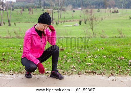 Young woman athlete feeling lightheaded or with headache on a cold winter day in the track of an urban park.