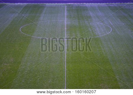 Green artificial grass soccer field with white line and center circle. Winter break.