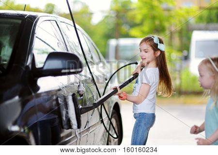 Two Adorable Little Sisters Washing A Car On A Carwash