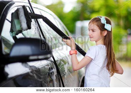 Adorable Little Girl Washing A Car On A Carwash