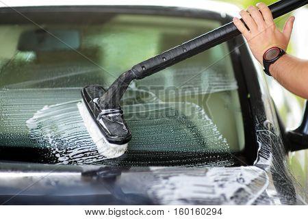 Using A Brush To Wash A Car On A Car Washing Facility