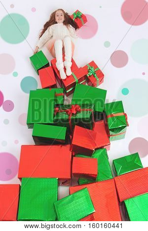 Merry Christmas 2016. Cute little girl holding Cristmas gift at the top of many gift boxes. Child happy to receive present. Shopping sale at Xmas. Cyber Monday US