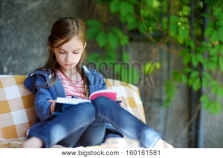 Cute Little Girl Reading A Book Outdoors