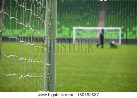 Beach soccer football goal through the net. Games in Brazil. Man mows the grass