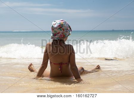 Little girl in panama sitting and looking at the sea with white waves. Thailand Phuket.
