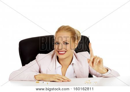 Smile buisness woman with several of cigarettes on the desk