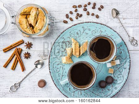Tasty and healthy almond cookies, rich in vitamins, minerals in a glass jar, cups of coffee,  almonds, chocolates, cinnamon, star anise and sugar on white wooden table. Top view.