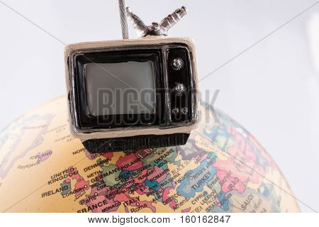 Retro syled tiny television model on a globe