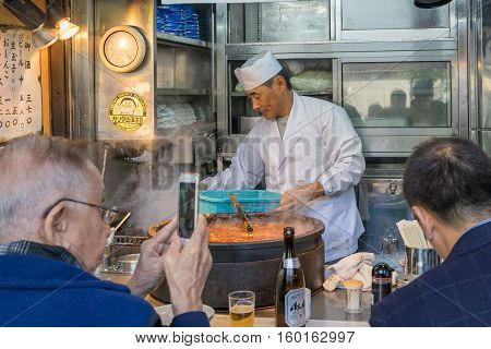 TOKYO, JAPAN - NOV 18, 2016: Many people shopping and eating some food at the Tsukiji market. The market consists of small shops and restaurants crowded along narrow lanes. Tokyo, Japan. NOV 18, 2016