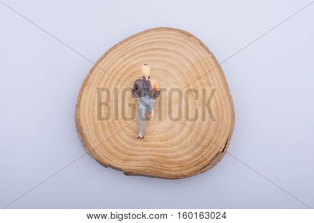 Man with crippled leg on a wood log cut in round pieces on a white background