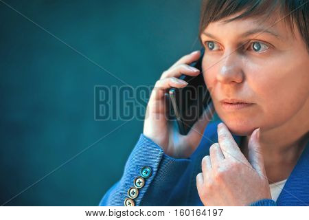 Worried businesswoman talking on mobile phone hand on the chin