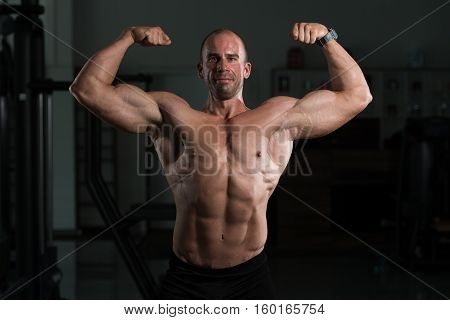Bodybuilder Fitness Model Posing Double Biceps After Exercises