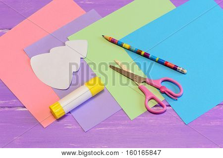 Stationery to create a Christmas greeting card from colored paper. Scissors, glue stick, pencil, colored paper pieces on lilac wooden background. Kids Christmas paper crafts in kindergarten or at home