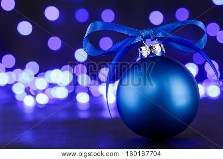 Blue christmas ball and blured purple blue and white lights at the background