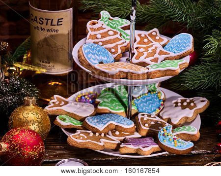 Christmas gingerbread cookies on Tiered Cookie Stand and white bottle wine. Wooden table and Christmas tree . Christmas tree and Christmas ball .