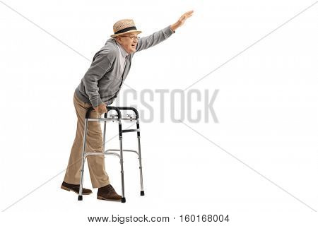 Full length profile shot of an elderly man with a walker waving isolated on white background