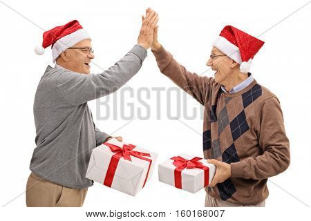Joyful seniors exchanging christmas gifts and high fiving each other isolated on white background