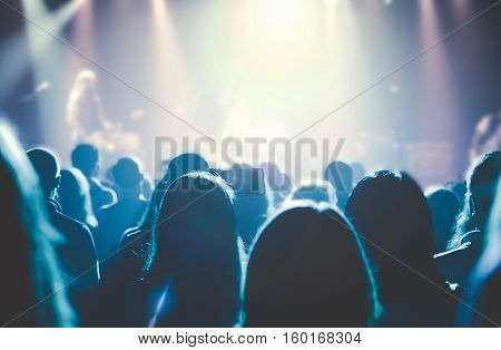 Female hands holding their smartphone and photographing rock concert. The concert hall is full of people at a rock concert