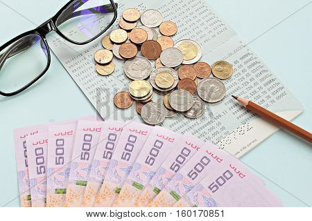 Business, finance or savings concept : Savings account passbook, Thai money baht, coins, glasses and pen on blue background