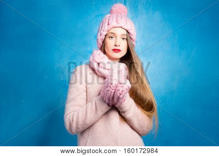 Winter portrait of a sad woman in knitted pink scurf, gloves and hat on the blue background