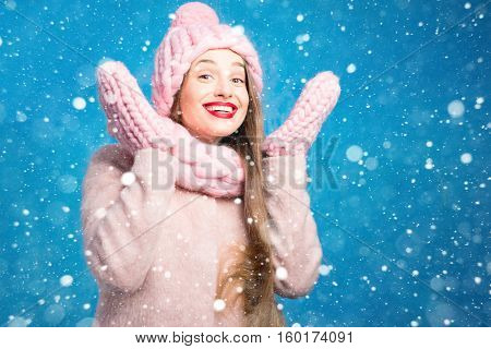 Winter portrait of a beautiful woman in knitted pink scurf, gloves and hat on the blue background during the snowfall