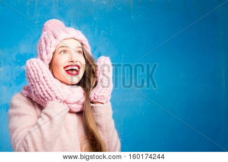 Winter portrait of a beautiful woman in knitted pink scurf, gloves and hat with snow flake on the blue background