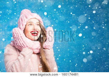 Winter portrait of a beautiful woman in knitted pink scurf, gloves and hat with snow flake on the blue background during the snowfall