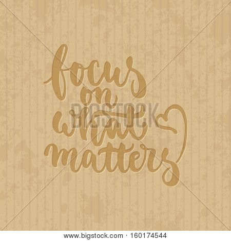 Focus on what matters - hand drawn lettering phrase isolated on the cardboard grunge background. Fun brush ink inscription for photo overlays, greeting card or t-shirt print, poster design.