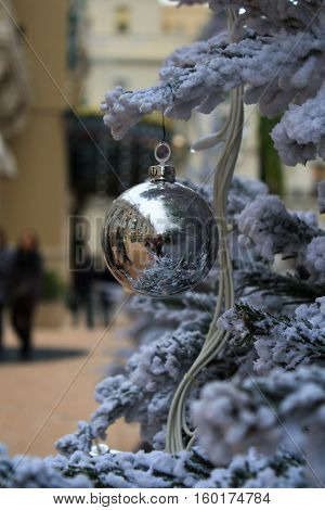 Merry Christmas Silver Ball on a snow-covered firtree in Monaco
