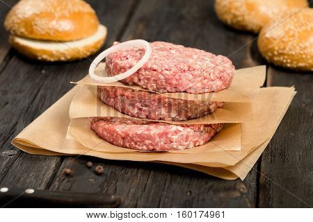 Closeup fresh raw ground beef meat cutlets with onion ring on a wooden table