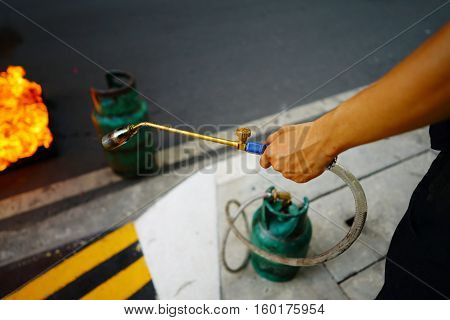 Men holding gas nozzle with blurred fire and gas tank on the ground floor selective focus