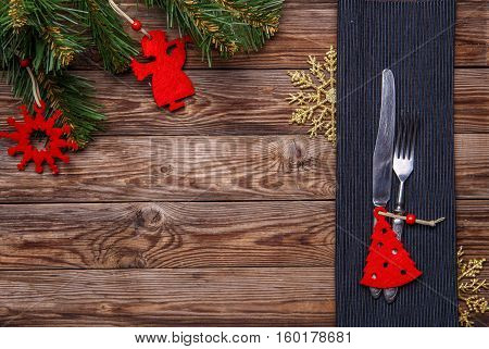 Christmas table place setting with fork and knife, decorated christmas toy - red fir-tree, gold snowflakes and christmas pine branches. Christmas holidays background.