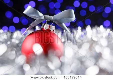 Red christmas ball and blured purple blue and white lights at the background