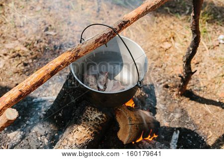 The fire near the camp. Cooking food on a fire. Journey into the wild concept.