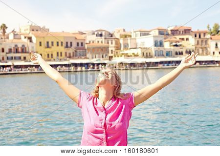 Happy woman standing by the sea with outstretched arms