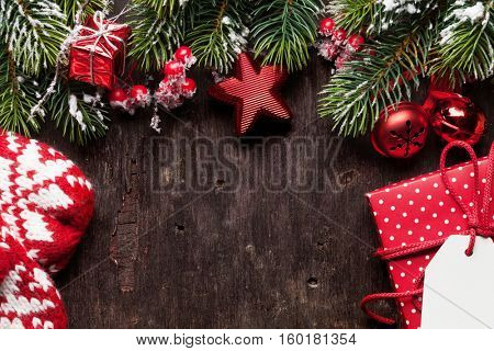 Christmas fir tree, decor, gift box and mittens over old wooden texture background. Top view with copy space for your greetings
