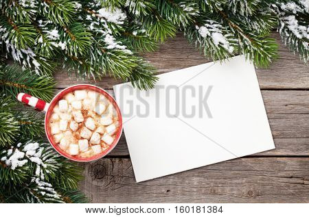 Christmas greeting card with fir tree and hot chocolate with marshmallow on wooden table. Top view with copy space