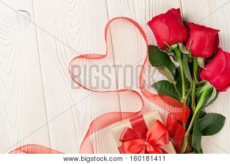 Red roses and heart shape ribbon over wooden table. Valentines day background. Top view with copy space