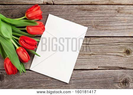 Red tulips and Valentine's day greeting card on wooden table. View with copy space