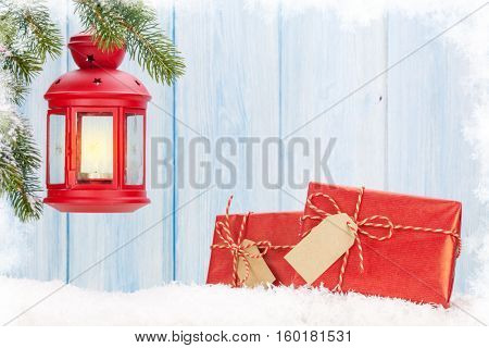 Christmas candle lantern, gift boxes and fir tree in snow. View with copy space