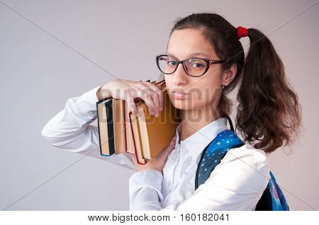 Schoolgirl with satchel on his shoulder holding a lot of book
