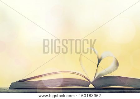 Love valentine's day or reading concept with heart shaped book on bokeh background copy space horizontal