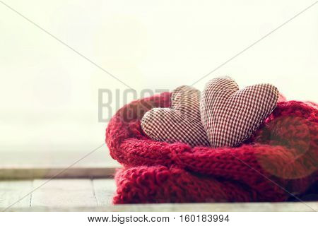 Beautiful red plush hearts with warm scarf on a bright background horizontal. Home winter valentine's day or love concept